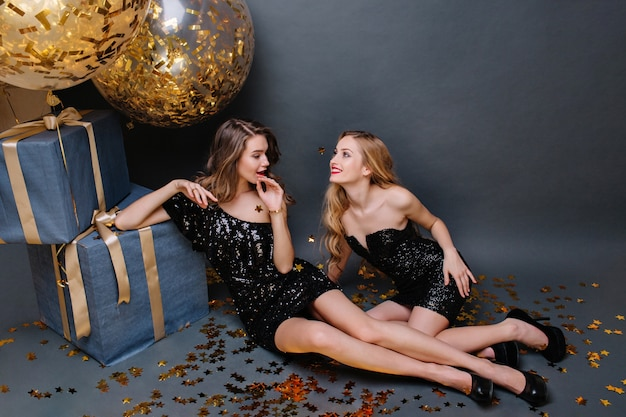 Dos hermosas mujeres jóvenes de moda en vestidos negros de lujo sentados en el piso. divertida, mirada elegante, cabello largo y rizado. gran regalo, globos dorados, oropel. Foto gratis