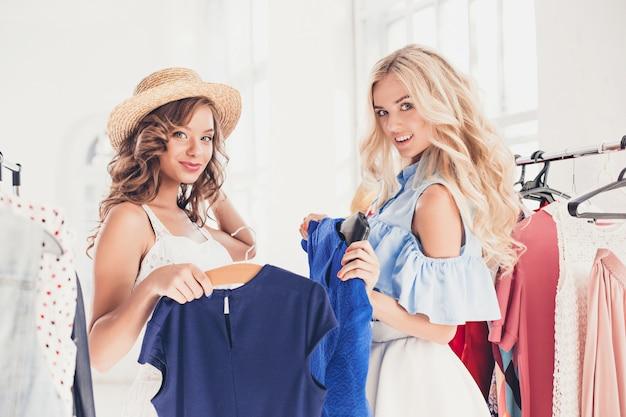 Las dos hermosas mujeres jóvenes que miran vestidos y se lo prueban mientras eligen en la tienda Foto gratis