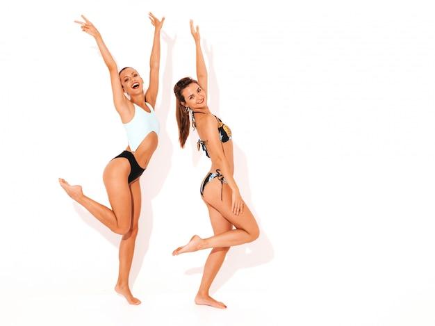 Dos hermosas mujeres sonrientes sexy en lencería de natación. modelos calientes de moda divirtiéndose. chicas aisladas levantando las manos, longitud completa Foto gratis