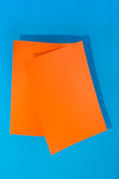Dos hojas de papel naranja sobre un fondo azul para decoración, para diseño de texto, para una plantilla Foto Premium