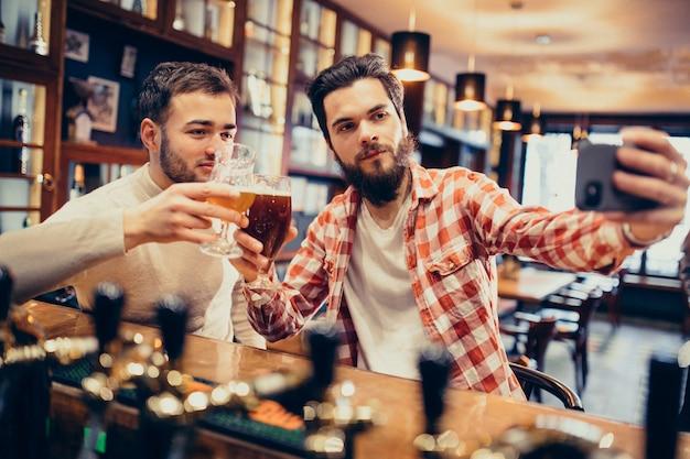 Dos hombre guapo con barba bebiendo cerveza en pub Foto gratis
