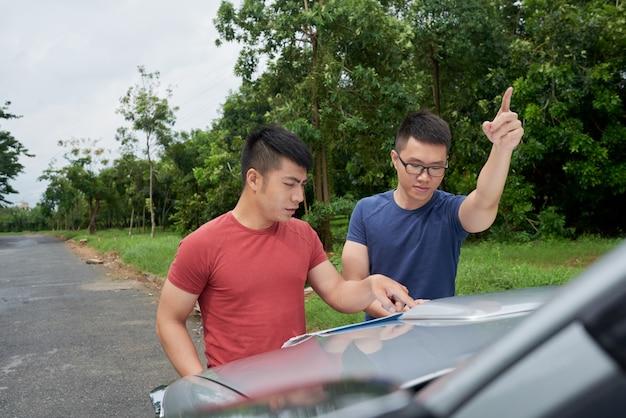 Dos hombres asiáticos de pie en coche en carretera, mirando el mapa y apuntando hacia adelante Foto gratis