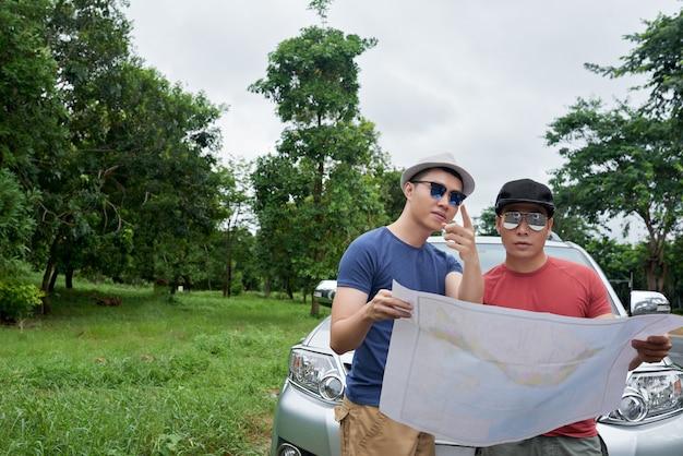 Dos hombres con gafas de sol de pie en coche, sosteniendo un gran mapa y señalando Foto gratis