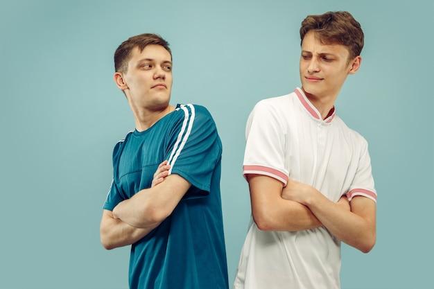 Dos hombres jóvenes en ropa deportiva aislados. aficionados al deporte, fútbol o club o equipo de fútbol. retrato de medio cuerpo de amigos. concepto de emociones humanas, expresión facial. Foto gratis