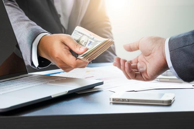 Dos hombres de negocios dan y toman billetes de dólar estadounidense. el dólar estadounidense es la moneda de cambio principal y popular en el mundo. inversión y pago Foto Premium