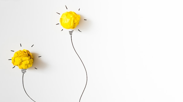 Dos iluminaron la bombilla de papel amarilla arrugada en el fondo blanco Foto gratis