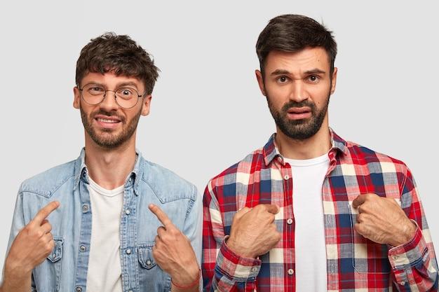 Dos jóvenes disgustados se señalan a sí mismos, preguntan por qué deberían hacer sus deberes en la casa, fruncen el ceño con descontento, usan camisas elegantes, tienen barba incipiente, aislados sobre una pared blanca Foto gratis