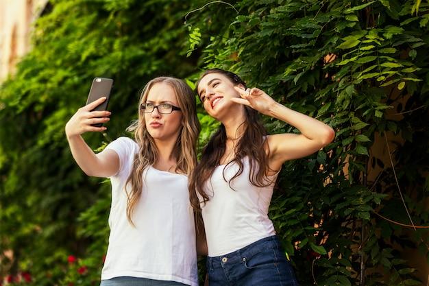 Dos jóvenes divertidas están tomando fotos selfie en el teléfono inteligente cerca de la pared de vegetación Foto gratis