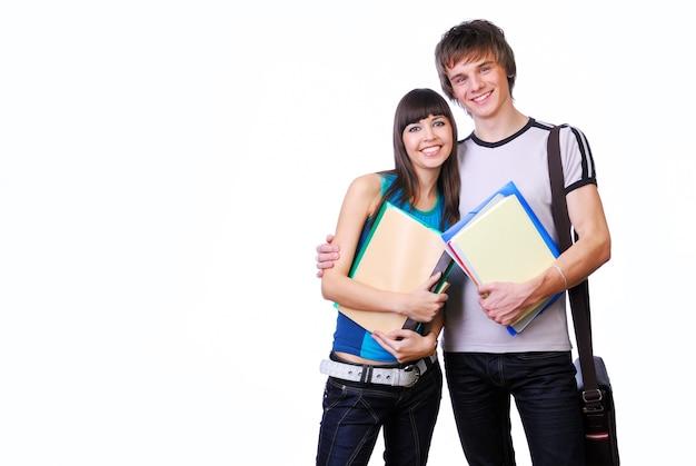 Dos jóvenes estudiantes adultos de pie y abrazando aislado en blanco Foto gratis
