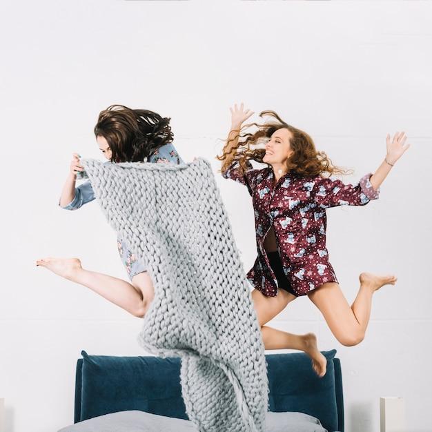 Dos jóvenes felices saltando sobre la cama Foto gratis