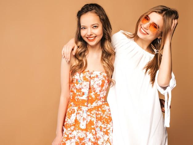 Dos jóvenes hermosas chicas sonrientes en ropa de moda de verano. sexy mujer despreocupada posando. modelos positivos en gafas de sol redondas. Foto gratis