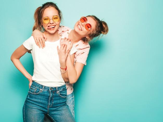 Dos jóvenes hermosas rubias sonrientes chicas hipster en ropa de jeans de moda hipster de verano. mujeres despreocupadas sexy posando junto a la pared azul. modelos modernos y positivos divirtiéndose en gafas de sol Foto gratis