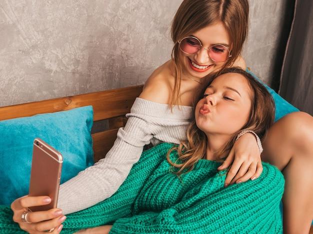 Dos jóvenes hermosas sonrientes hermosas chicas en ropa de moda de verano. mujeres despreocupadas sexy posando en el interior y tomando selfie. modelos positivos divirtiéndose con el teléfono inteligente. Foto gratis