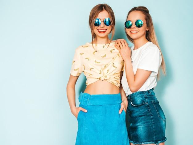 Dos jóvenes hermosas sonrientes rubias hipster chicas en jeans moda verano faldas ropa. Foto gratis