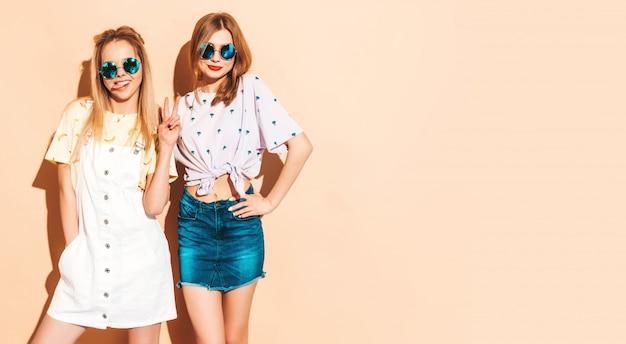 Dos jóvenes hermosas sonrientes rubias hipster chicas en ropa de verano colorida camiseta. y mostrando la lengua Foto gratis