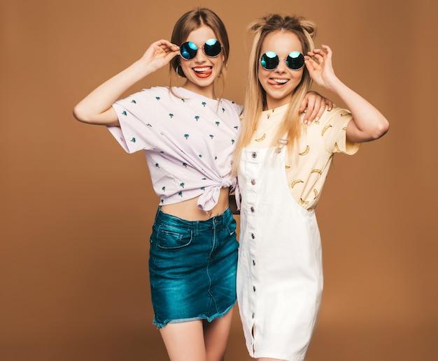 Dos jóvenes hermosas sonrientes rubias hipster chicas en ropa de verano colorida camiseta. mujeres despreocupadas atractivas que presentan en fondo beige en gafas de sol redondas. modelos positivos divirtiéndose y mostrando a Foto gratis