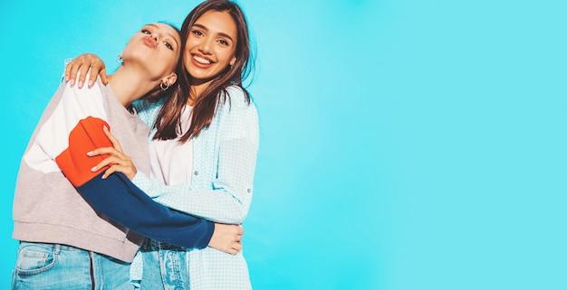 Dos jóvenes hermosas sonrientes rubias hipster chicas en ropa de verano colorida camiseta. mujeres despreocupadas sexy posando junto a la pared azul. modelos positivos divirtiéndose y haciendo cara de pato Foto gratis