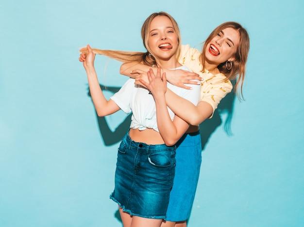 Dos jóvenes hermosas sonrientes rubias hipster chicas en ropa de verano colorida camiseta. mujeres despreocupadas sexy posando junto a la pared azul. modelos positivos divirtiéndose y mostrando la lengua Foto gratis
