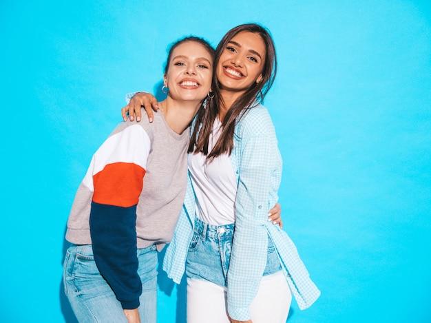 Dos jóvenes hermosas sonrientes rubias hipster chicas en ropa de verano colorida camiseta. mujeres despreocupadas sexy posando junto a la pared azul. modelos positivos divirtiéndose Foto gratis