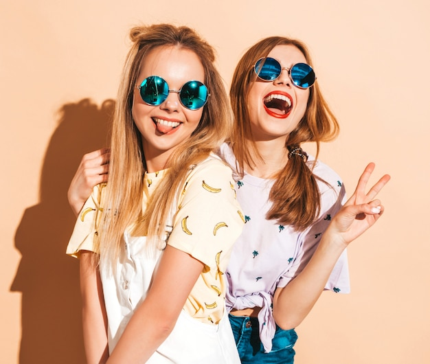 Dos jóvenes hermosas sonrientes rubias hipster chicas en ropa de verano colorida camiseta. mujeres despreocupadas sexy posando junto a la pared de color beige en gafas de sol redondas. mostrando signo de paz Foto gratis