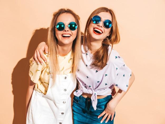 Dos jóvenes hermosas sonrientes rubias hipster chicas en ropa de verano colorida camiseta. Foto gratis