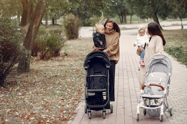 Dos jóvenes madres caminando en un parque de otoño con carruajes Foto gratis