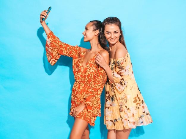 Dos jóvenes sonrientes mujeres hipster en vestidos hippie de verano. chicas tomando fotos de autorretrato en smartphone. modelos posando junto a la pared azul en el estudio. mujer mostrando emociones positivas. Foto gratis