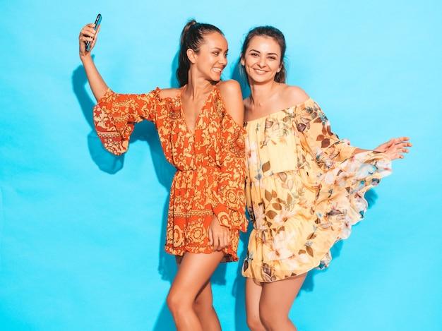 Dos jóvenes sonrientes mujeres hipster en vestidos hippie de verano. chicas tomando fotos de autorretrato en smartphone. modelos posando junto a la pared azul en el estudio Foto gratis