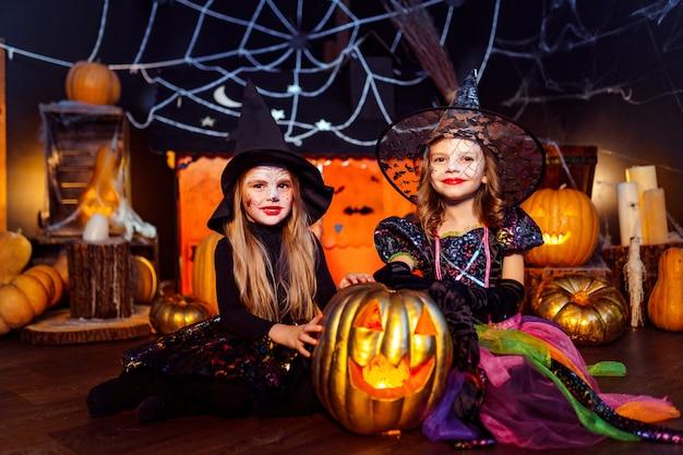 Dos lindas hermanas divertidas celebran la fiesta. niños alegres en trajes de carnaval listos para halloween. Foto Premium