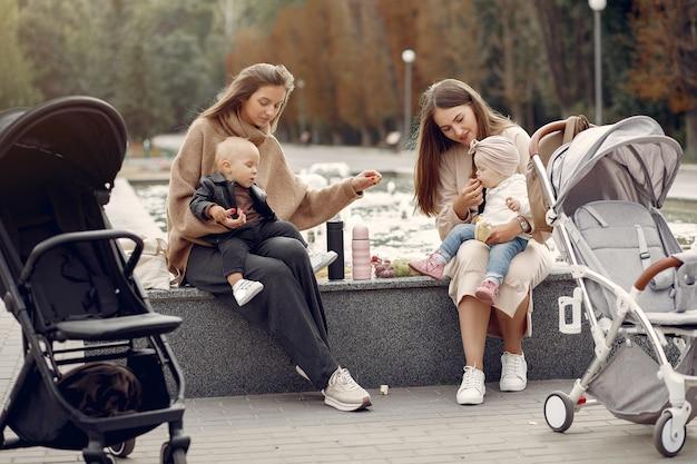 Dos madres jóvenes sentadas en un parque de otoño con carruajes Foto gratis