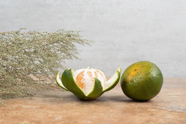 Dos mandarinas frescas sobre fondo de mármol. Foto gratis