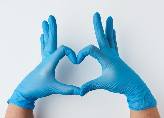 Dos manos en guantes médicos estériles de látex azul muestra un gesto del corazón sobre una superficie blanca Foto Premium