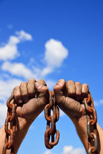 Dos manos de hombre en el barro sostienen una cadena de metal oxidado. Foto Premium