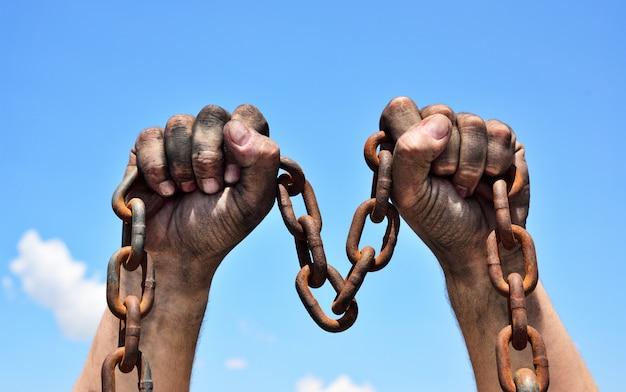 Dos manos masculinas sosteniendo una cadena de metal oxidado Foto Premium