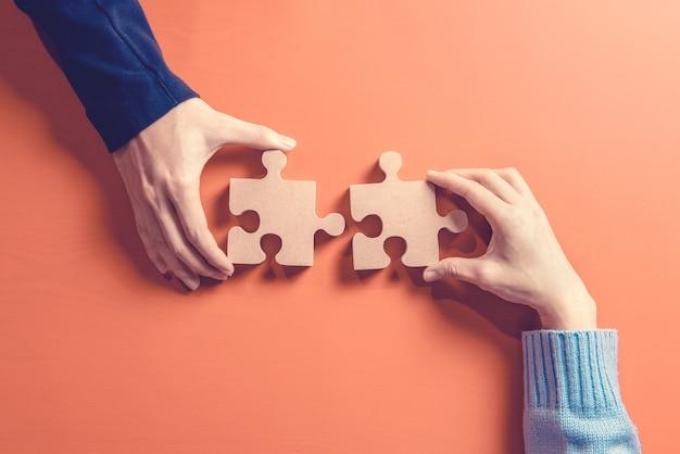 Dos manos sosteniendo rompecabezas, concepto de trabajo en equipo construyendo un éxito. Foto Premium