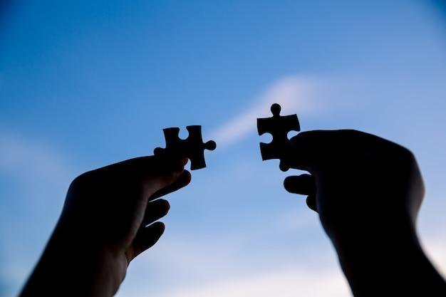 Dos manos tratando de conectar la pieza del rompecabezas de pareja con el fondo del atardecer. Foto gratis