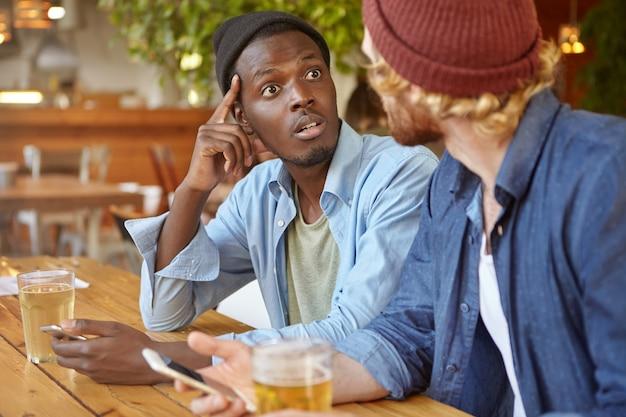 Dos mejores amigos o compañeros de la universidad tomando cerveza y usando aparatos electrónicos en el pub: un hombre afroamericano hablando con su amigo caucásico irreconocible, mirándolo en estado de shock e incredulidad Foto gratis