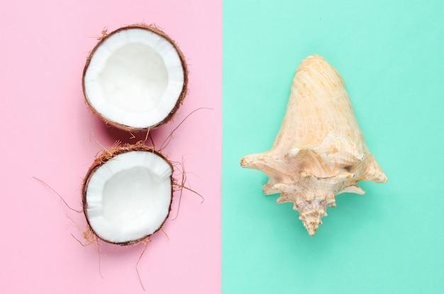 Dos mitades de coco picado y concha sobre fondo azul pastel rosa Foto Premium
