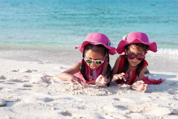 Dos muchachas asiáticas lindas del niño que llevan el sombrero rosado y las gafas de sol que juegan con la arena junta en la playa Foto Premium