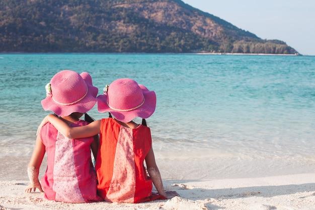 Dos muchachas asiáticas lindas del pequeño niño que se sientan y que se abrazan en la playa Foto Premium