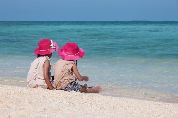 Dos muchachas asiáticas lindas del pequeño niño que se sientan y que juegan con la arena juntas en la playa Foto Premium