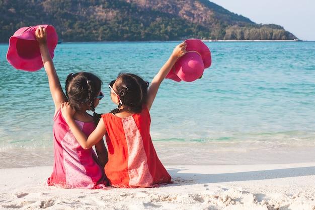 Dos muchachas asiáticas lindas del pequeño niño que sostienen el sombrero que se sienta y que juega junto en la playa Foto Premium