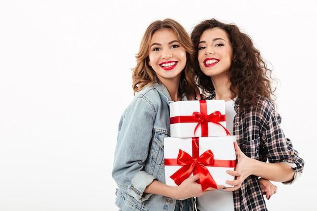 Dos muchachas sonrientes que presentan con los regalos sobre la pared blanca Foto gratis