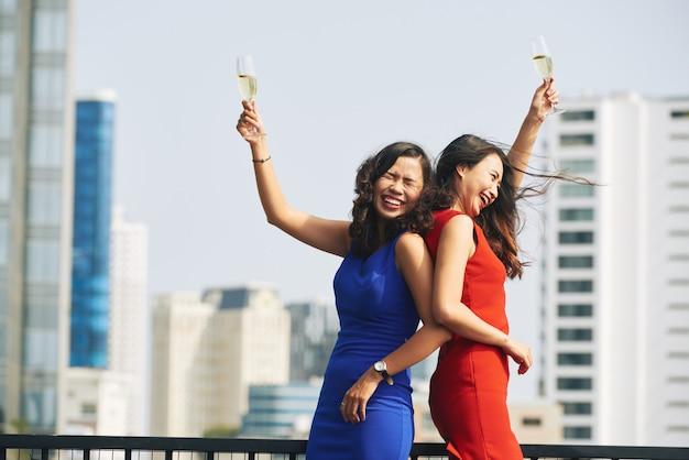 Dos mujeres asiáticas con vestidos brillantes sosteniendo copas de champán en una fiesta urbana en la azotea Foto gratis