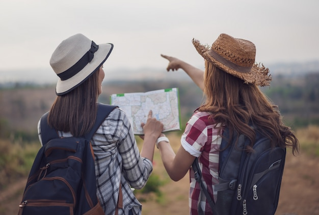Dos mujeres buscando la dirección en el mapa de ubicación mientras viaja Foto Premium