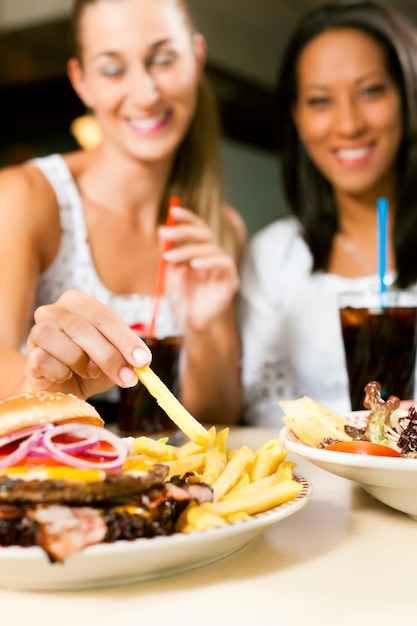 Dos mujeres comiendo hamburguesas y bebiendo refrescos Foto Premium