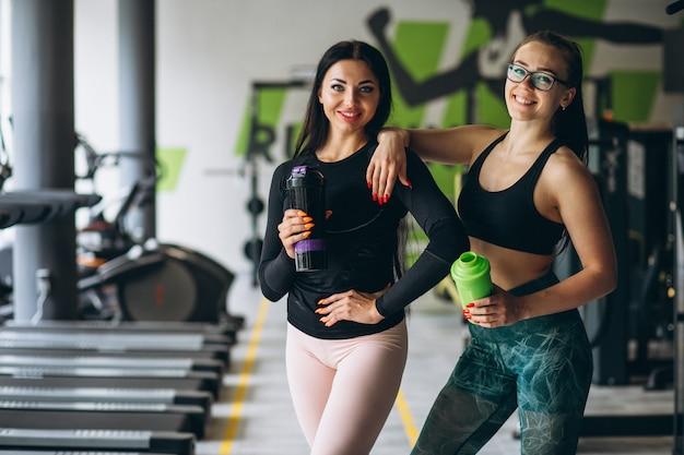 Dos mujeres entrenando juntas en el gimnasio Foto gratis