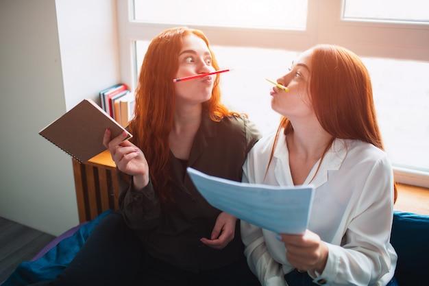 Dos mujeres jóvenes están cansadas y se divierten. imitan un bigote con la ayuda de lápices multicolores. dos estudiantes pelirrojos estudian en casa o en un dormitorio estudiantil. se están preparando para los exámenes. Foto Premium
