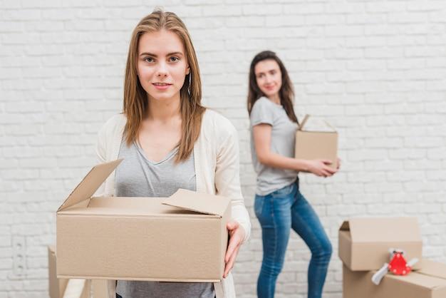 Dos mujeres lesbianas con cajas de cartón en la mano de pie cerca de la pared de ladrillo blanco Foto gratis