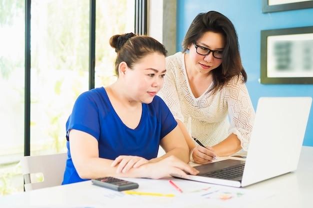 Dos mujeres de negocios están trabajando con la computadora en la oficina. Foto gratis